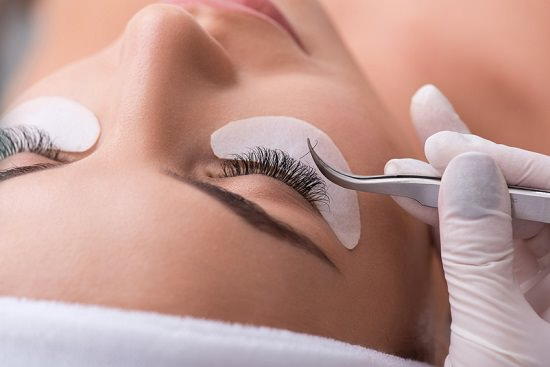 Close up of beautician hand in glove lengthening female lashes artificially. She is holding tweezers with fake eyelash